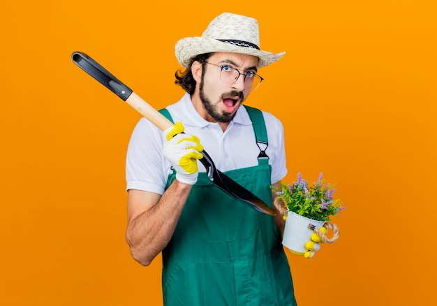 オレンジ色の壁の上に立って混乱しているように見えるシャベルと鉢植えの植物を保持しているジャンプスーツと帽子を身に着けている若いひげを生やした庭師の男