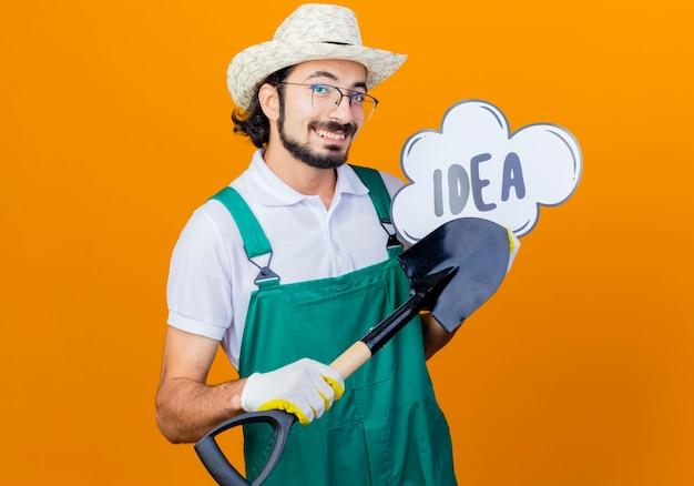オレンジ色の壁の上に立って幸せそうな顔で笑顔で正面を見て単語のアイデアとシャベルと吹き出しのサインを保持しているジャンプスーツと帽子を身に着けている若いひげを生やした庭師の男