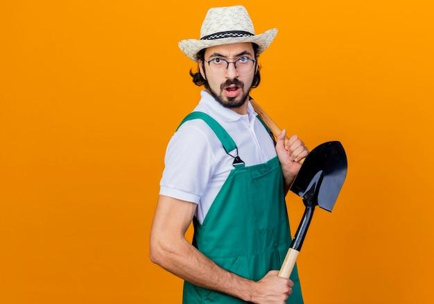 オレンジ色の壁の上に立って混乱して正面を見てシャベルを保持しているジャンプスーツと帽子を身に着けている若いひげを生やした庭師の男