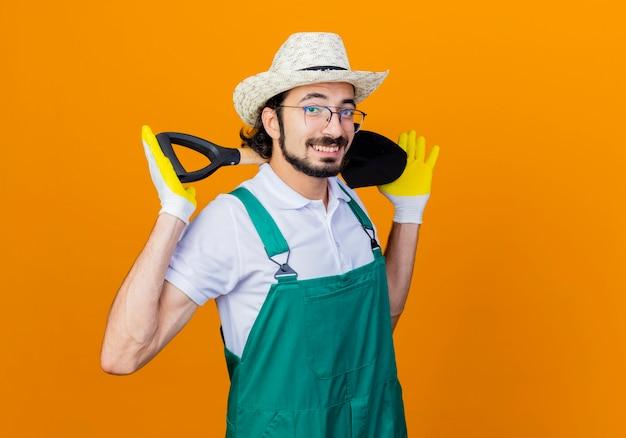 Молодой бородатый садовник в комбинезоне и шляпе держит лопату, глядя вперед, весело улыбаясь, стоя над оранжевой стеной