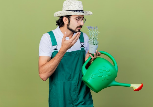 じょうろと鉢植えの植物を保持しているジャンプスーツと帽子を身に着けている若いひげを生やした庭師の男は、薄緑色の壁の上に立って心地よい香りを感じます