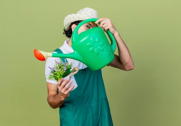 じょうろと薄緑色の壁の上に立っている顔を隠す鉢植えの植物を保持しているジャンプスーツと帽子を身に着けている若いひげを生やした庭師の男