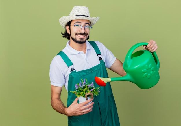 じょうろと鉢植えの植物を保持しているジャンプスーツと帽子を身に着けている若いひげを生やした庭師の男は、薄緑色の壁の上に立っている幸せそうな顔で笑顔で正面を見て