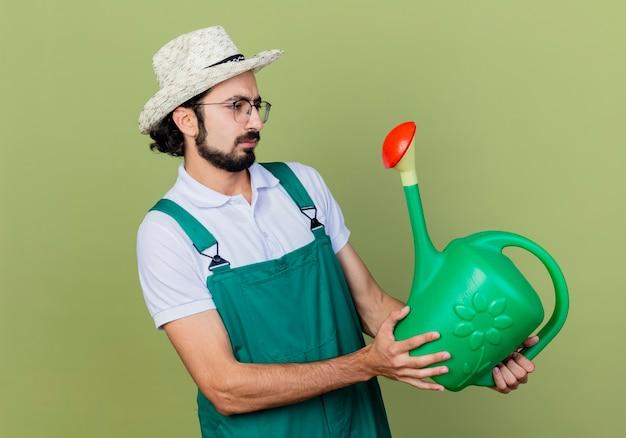 じょうろを持ったジャンプスーツと帽子をかぶった若いひげを生やした庭師の男は、薄緑色の壁の上に立って驚いてそれを見ることができます