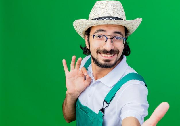녹색 벽 위에 서있는 확인 서명을 보여주는 웃 고 앞을보고 죄수 복과 모자를 쓰고 젊은 수염 정원사 남자