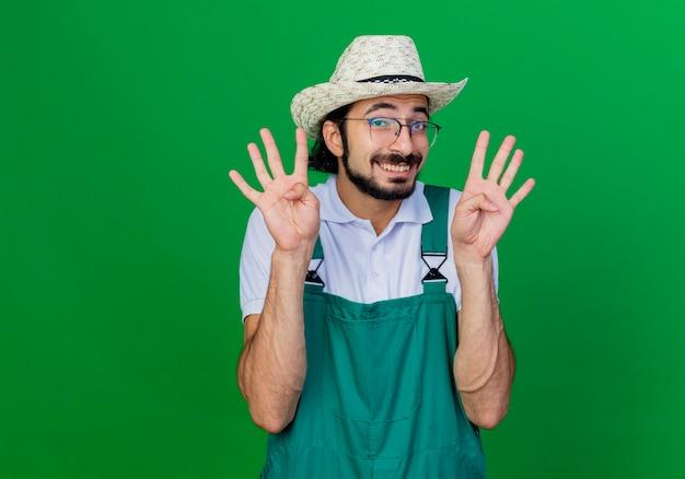 ジャンプスーツと帽子をかぶって笑顔の若いひげを生やした庭師の男は8番を示しています