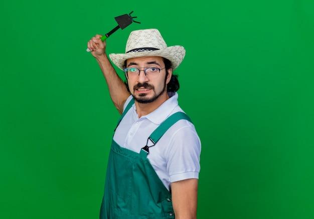 緑の壁の上に立っている怒った顔でマットックを振るジャンプスーツと帽子を身に着けている若いひげを生やした庭師の男