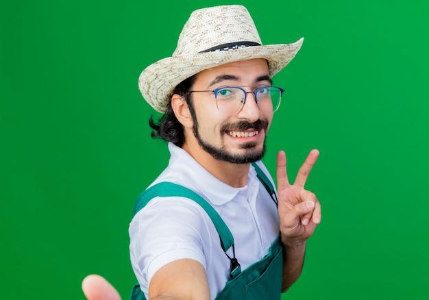 Giovane giardiniere barbuto uomo che indossa tuta e cappello facendo selfie sorridente che mostra v-segno in piedi sopra la parete verde