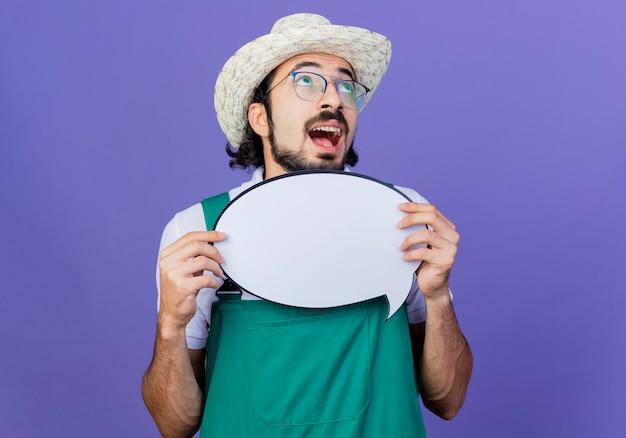 Giovane giardiniere barbuto uomo che indossa tuta e cappello che tiene il segno in bianco della bolla di discorso che osserva in su felice ed eccitato che sta sopra la parete blu