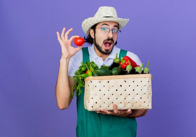 Giovane giardiniere barbuto uomo che indossa tuta e cappello tenendo la cassa piena di verdure che mostra il pomodoro fresco di essere sorpreso in piedi sopra la parete blu