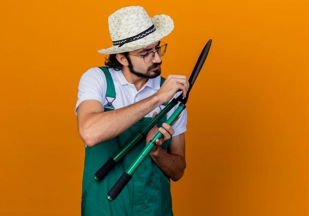 Giovane giardiniere barbuto uomo che indossa tuta e cappello holding tagliasiepi guardando clippers con faccia seria in piedi sopra la parete arancione