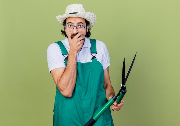Young bearded gardener man wearing jumpsuit and hat holding hedge clippers looking surprised and amazed standing over light green wall