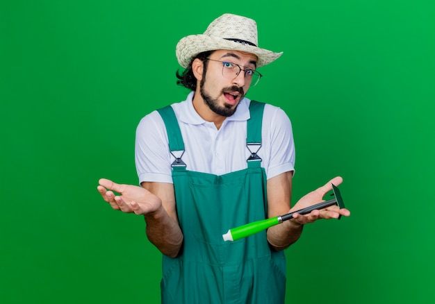 Young bearded gardener man wearing jumpsuit and hat holding mattock being confused spreading arms to the sides