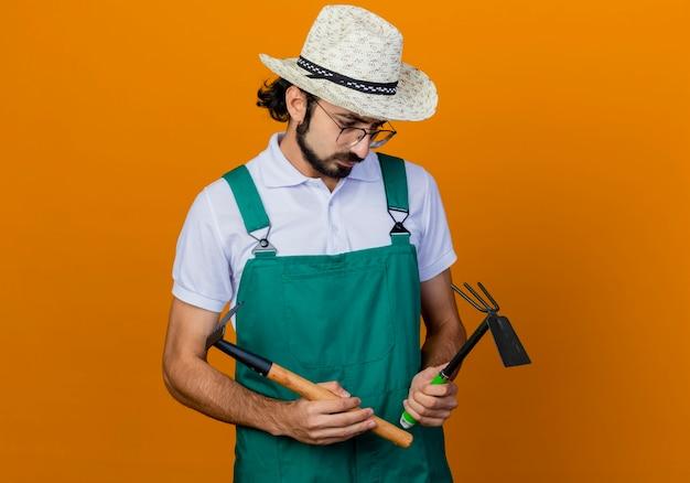 Giovane giardiniere barbuto uomo che indossa tuta e cappello azienda mattock e mini rastrello guardandoli confusi in piedi sopra la parete arancione