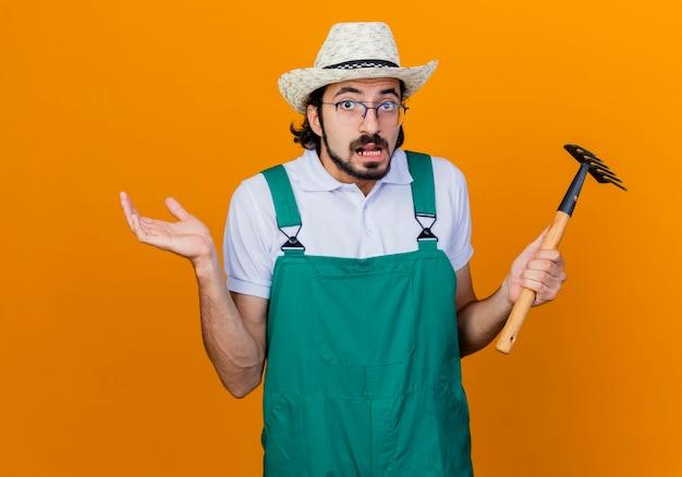 Giovane giardiniere barbuto uomo che indossa tuta e cappello azienda mini rastrello guardando davanti scrollare le spalle essendo confuso in piedi sopra la parete arancione