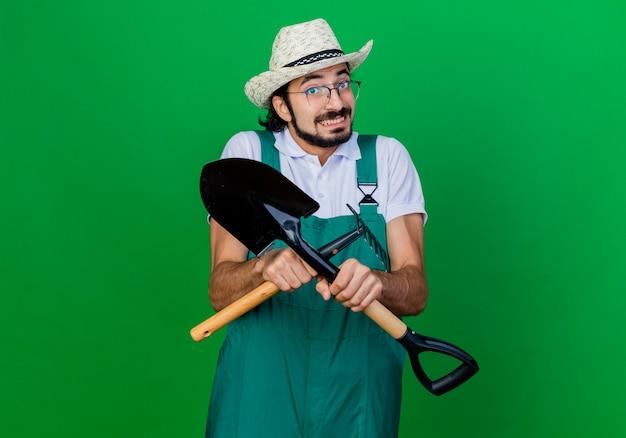 Giovane giardiniere barbuto uomo che indossa tuta e cappello che tiene mini rastrello e pala confusi