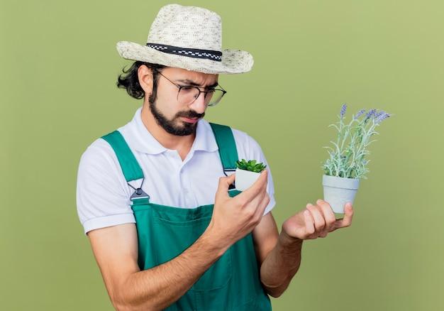 Giovane giardiniere barbuto uomo che indossa tuta e cappello tenendo le piante in vaso guardandole con espressione triste in piedi sopra il muro verde chiaro