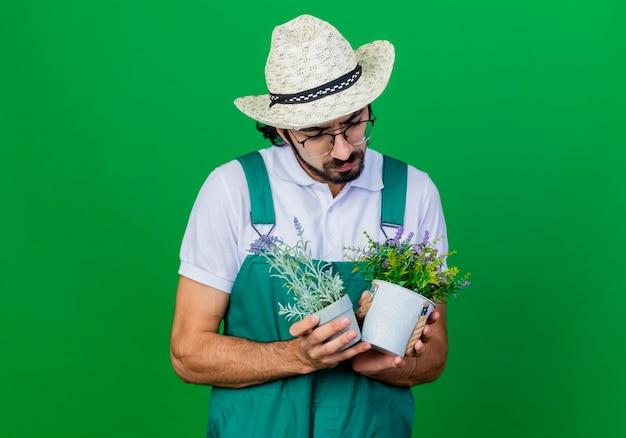 Giovane giardiniere barbuto uomo che indossa tuta e cappello che tiene piante in vaso guardandoli con faccia seria