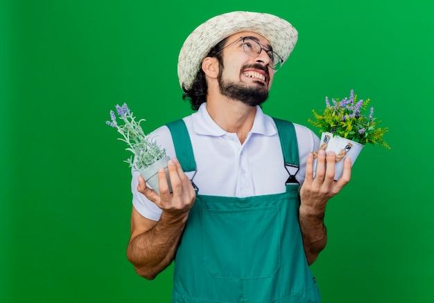Giovane giardiniere barbuto uomo che indossa tuta e cappello che tiene piante in vaso alzando lo sguardo con irritato exression