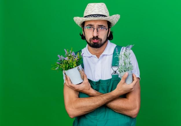 Giovane giardiniere barbuto uomo che indossa tuta e cappello che tiene piante in vaso con espressione triste