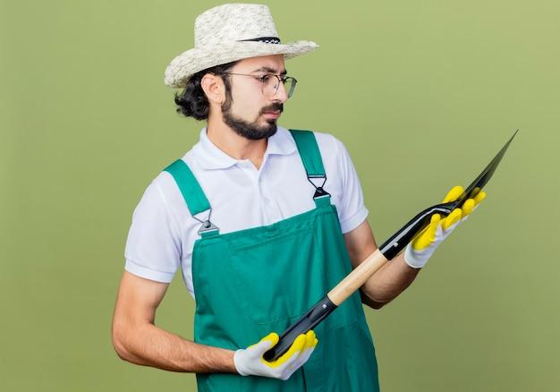 Giovane giardiniere barbuto uomo che indossa tuta e cappello tenendo la pala guardandolo perplesso