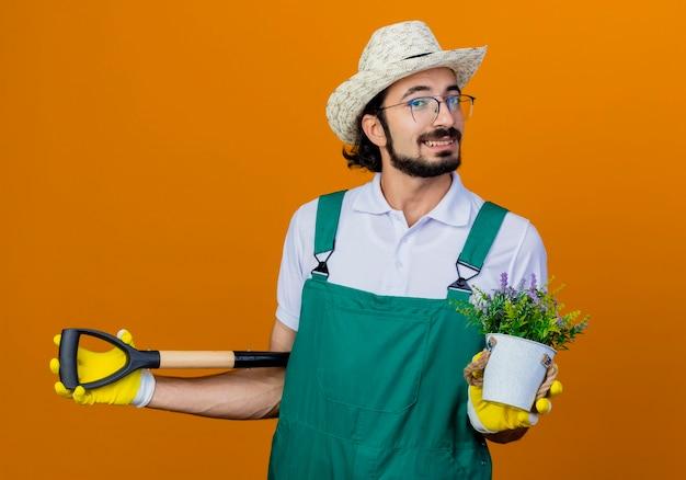 Giovane giardiniere barbuto uomo che indossa tuta e cappello tenendo la pala e la pianta in vaso sorridente felice e positivo