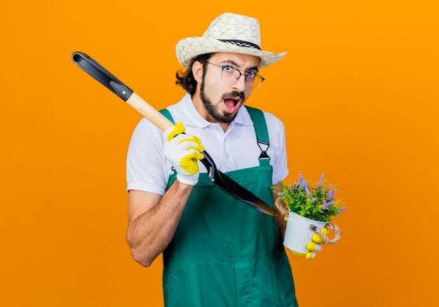 Giovane giardiniere barbuto uomo che indossa tuta e cappello tenendo la pala e pianta in vaso cercando confuso in piedi sopra la parete arancione