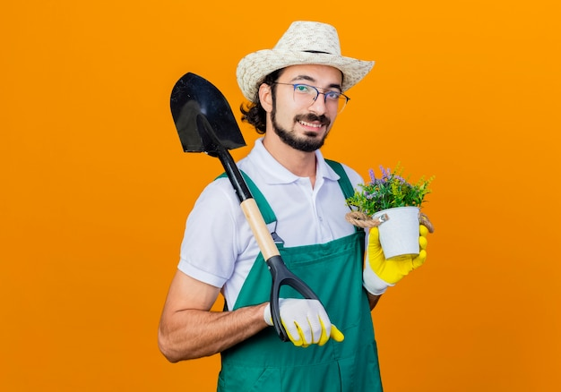 Young bearded gardener man wearing jumpsuit and hat holding shovel and potted plant looking at front smiling with happy face standing over orange wall