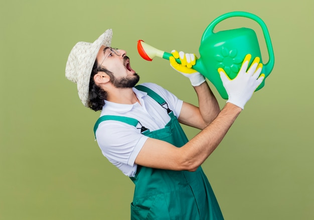 Young bearded gardener man wearing jumpsuit and hat holding watering can opening mouth wants to drink standing over light green wall