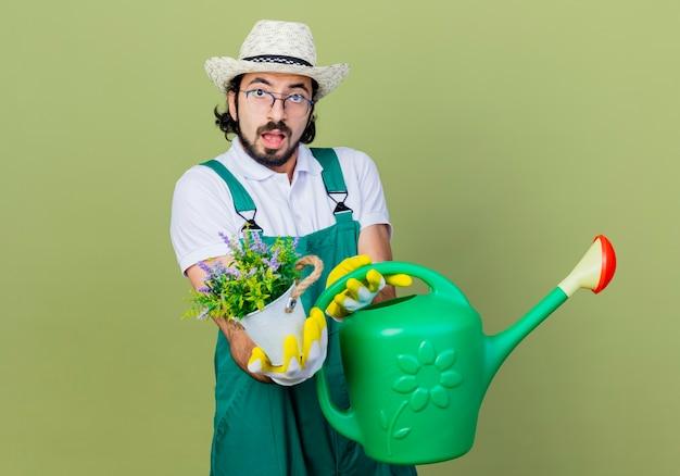 Giovane giardiniere barbuto uomo che indossa tuta e cappello azienda annaffiatoio e pianta in vaso guardando la parte anteriore confusa in piedi sopra il muro verde chiaro