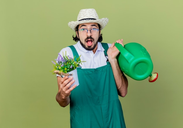 Young bearded gardener man wearing jumpsuit and hat holding watering can and potted plant looking at front being surprised and amazed standing over light green wall