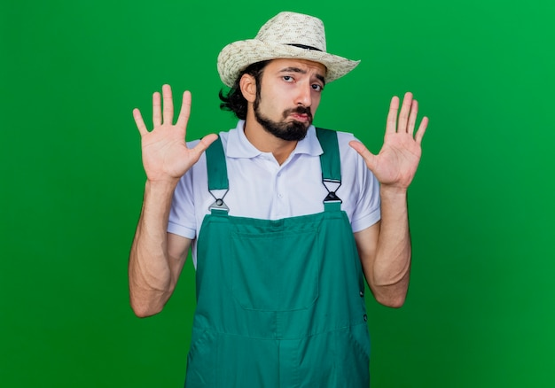 Young bearded gardener man wearing jumpsuit and hat raising hands being confused having no answer