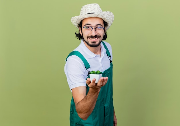 Young bearded gardener man wearing jumpsuit and hat showing potted plant looking at front smiling with happy face standing over light green wall