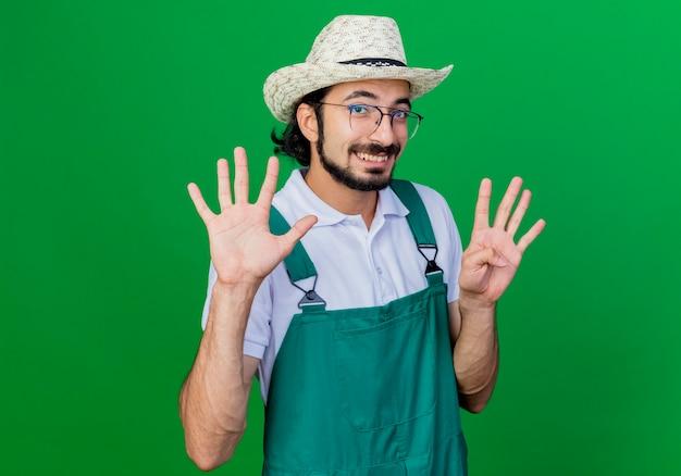 Giovane giardiniere barbuto uomo che indossa tuta e cappello sorridente che mostra il numero nove
