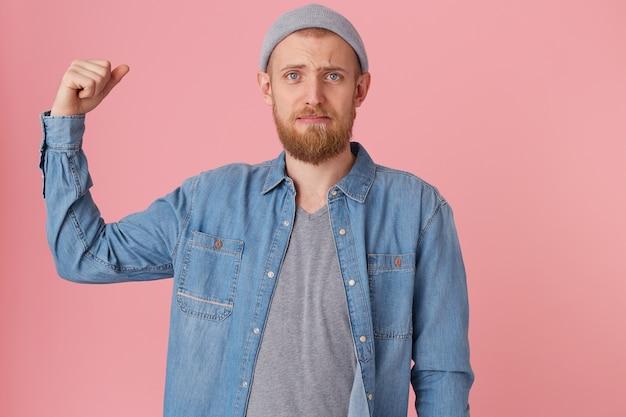 Un giovane barbuto non può vantarsi della sua forza, scontento della sua forma fisica, ha alzato il braccio piegato per dimostrare i muscoli deboli, con sguardo dispiaciuto, vestito con una camicia di jeans