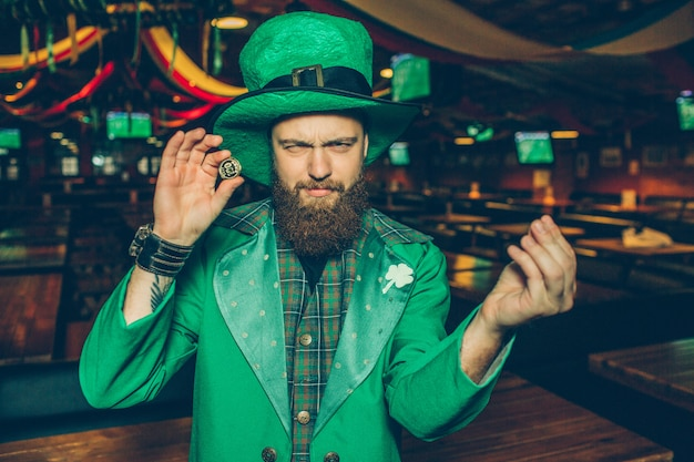 Young bearded guy in green suit hold golden coin in hands. he look calm and peaceful. young man stand alone in pub. he wear st. patrick's suit.
