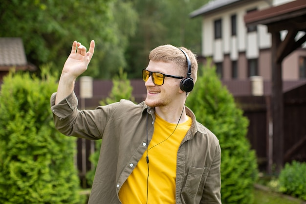 Young bearded guy greets someone with wave of his hand listening to music online through modern headphones outdoors outdoors on sunny summer day