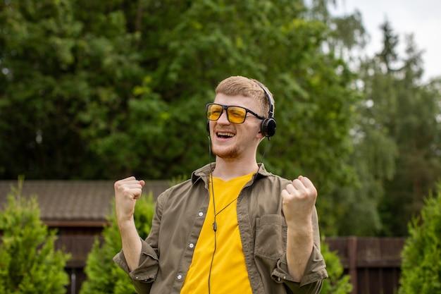 黄色いメガネをかけた若いひげを生やした男は、ヘッドフォンで音楽を聴き、緑の背景に手をジェスチャーで楽しく歌っています。