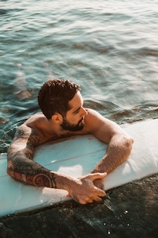 Young bearded guy lying on surf board in water
