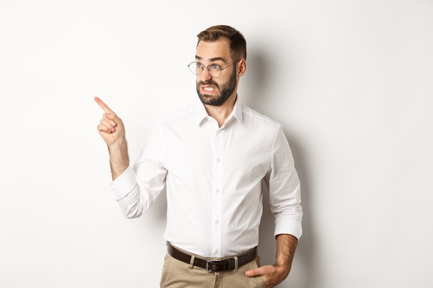 Young bearded guy seeing something disturbing, cringe while pointing finger left at promo offer, standing awkward against white background.