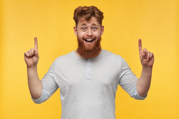 빨간 머리를 가진 젊은 수염 난 남자는 노란색에 복사 공간에서 위쪽으로 손가락으로 행복하고 웃는 포인트를 느낍니다.