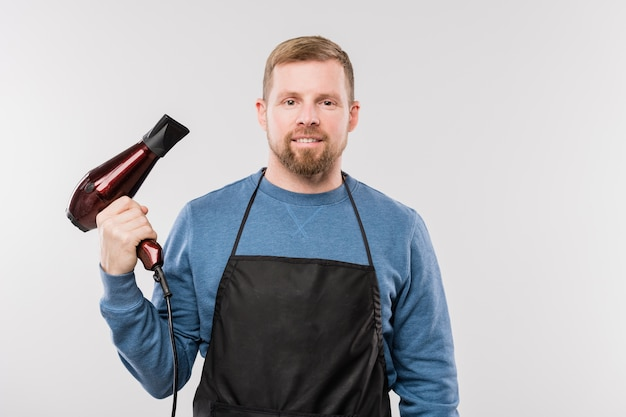 Young bearded hairdresser in apron and blue pullover holding hairdryer while standing in isolation