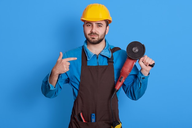 Young bearded handsome builder looking , holding angle grinder in one hand and pointing at tool with index finger, foreman wearing protective helmet, uniform and brown apron.