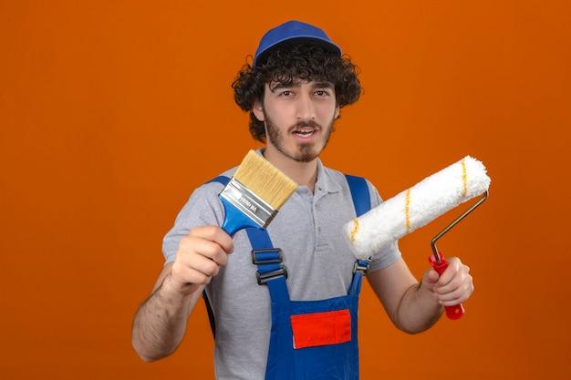 若いひげを生やしたハンサムなビルダー建設ユニフォームとキャップを保持しているペイントローラーと孤立したオレンジ色の壁に笑みを浮かべてブラシを身に着けて