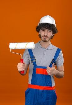 Молодой бородатый красивый строитель в строительной форме и защитном шлеме, держащий валик с краской, уверенно показывает пальцем вверх над изолированной оранжевой стеной