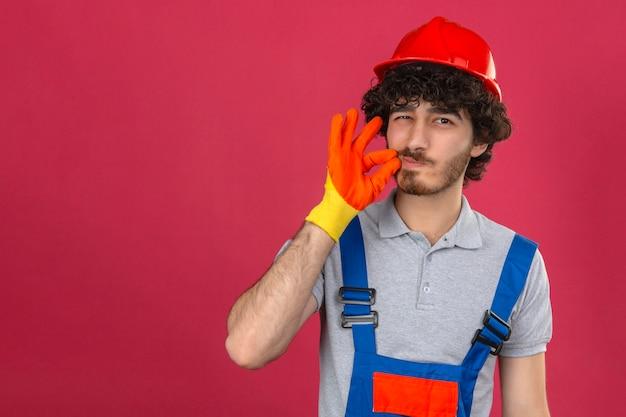 Молодой бородатый красивый строитель в строительной форме и защитном шлеме делает жест тишины, словно закрывает рот на молнии над изолированной розовой стеной