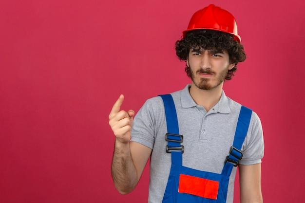 Молодой бородатый красивый строитель в строительной форме и защитном шлеме, указывая пальцем вверх и сердитым выражением лица, не показывающим жестов над изолированной розовой стеной