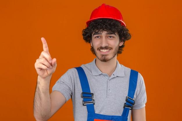 若いひげを生やしたハンサムなビルダー建設ユニフォームと安全ヘルメットを身に着けている孤立したオレンジ色の壁の上に陽気に人差し指を笑って