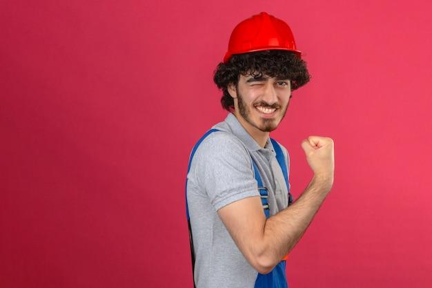 고립 된 분홍색 벽 위에 승자 같은 그의 팔뚝을 보여주는 건설 유니폼과 안전 헬멧 윙크를 입고 젊은 수염 잘 생긴 작성기 무료 사진