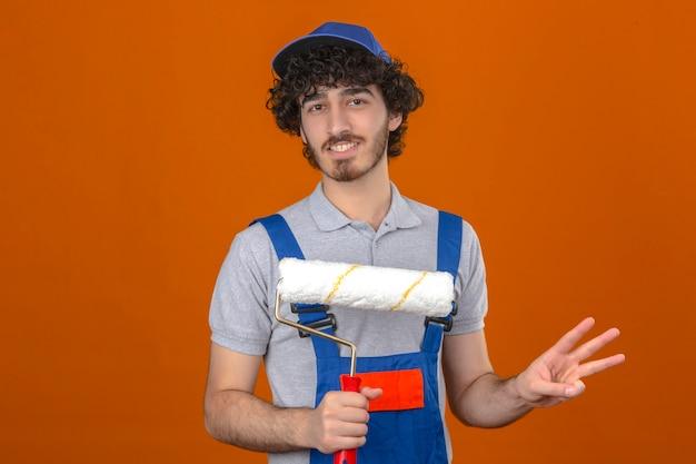 Il giovane costruttore bello barbuto che indossa l'uniforme della costruzione e ricopre il rullo di pittura della tenuta che mostra e che indica su con le dita il numero tre mentre sorride sicuro sopra il backgr arancio isolato